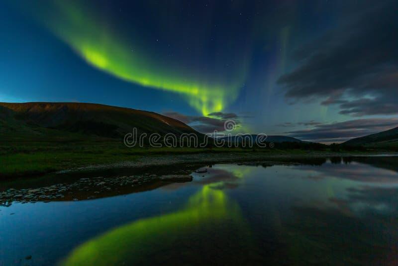 Aurora borealis in de besnoeiingsbergen van de nachthemel, in water worden weerspiegeld dat stock foto's