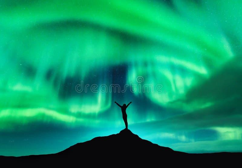 Aurora borealis e siluetta di una donna con le armi su alzate immagine stock