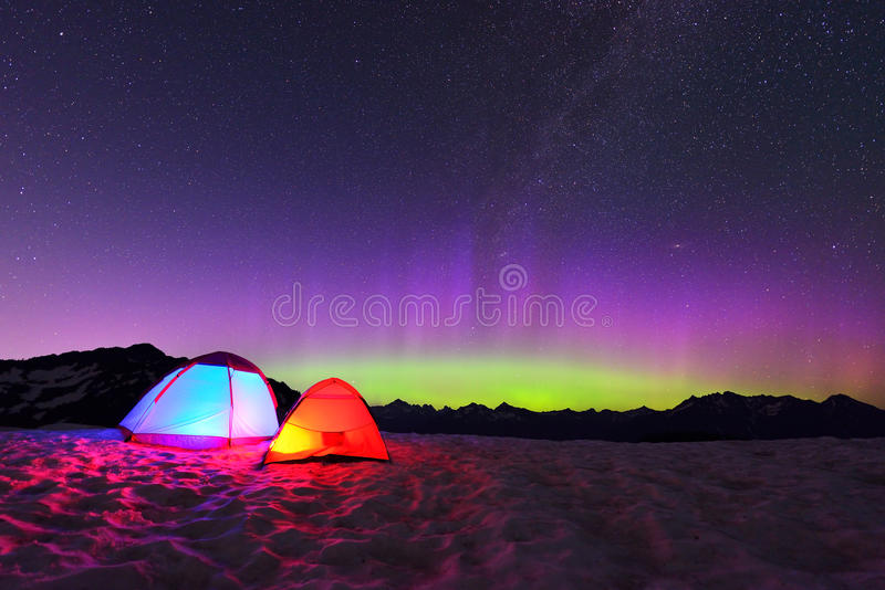 Aurora borealis e tende sulla montagna della neve immagine stock libera da diritti