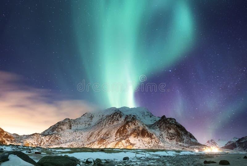 Aurora borealis en las islas de Lofoten, Noruega Aurora boreal verde sobre las montañas Cielo nocturno con las luces polares Invi fotografía de archivo libre de regalías