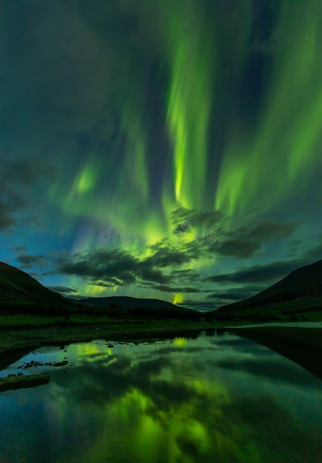 Aurora borealis en las monta?as del corte del cielo nocturno, reflejadas en agua imagen de archivo libre de regalías