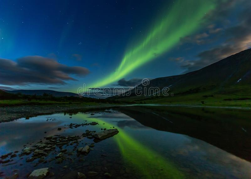 Aurora borealis en las monta?as del corte del cielo nocturno, reflejadas en agua fotos de archivo libres de regalías
