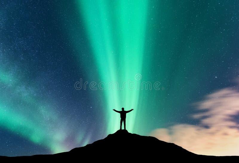 Aurora borealis en silhouet van de bevindende mens royalty-vrije stock foto's