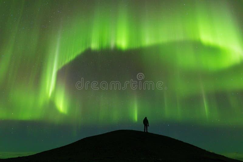 Aurora borealis en silhouet van de bevindende mens Jokulsarlon, IJsland Dageraad en gelukkige mens Hemel met sterren en groene po stock afbeeldingen