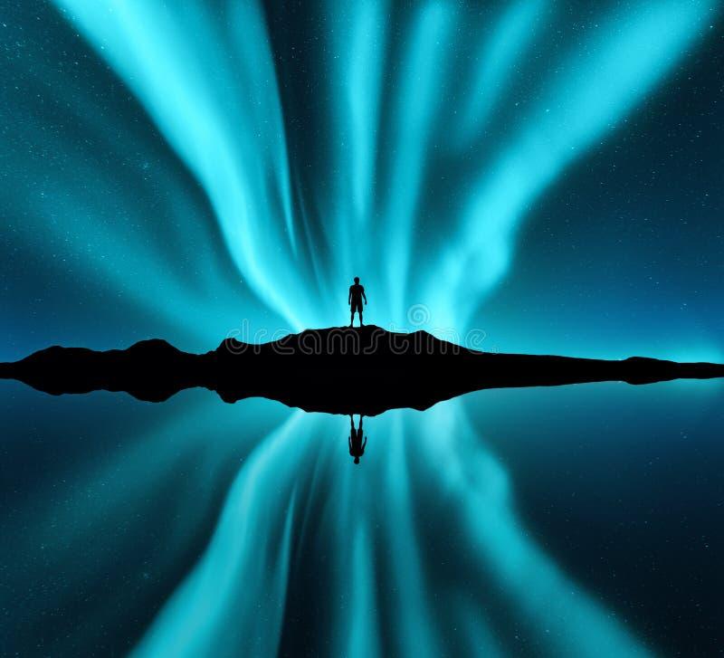 Aurora borealis et silhouette d'homme debout sur la colline images stock