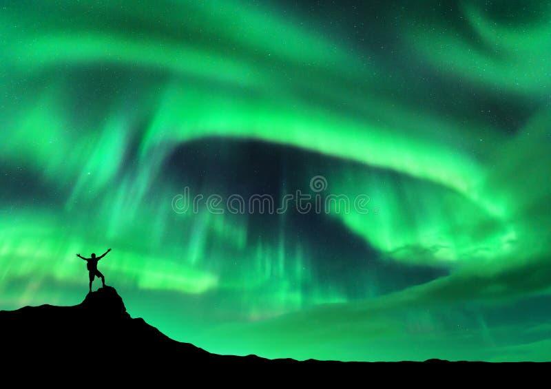 Aurora borealis et silhouette d'un homme avec augmentés les bras photographie stock