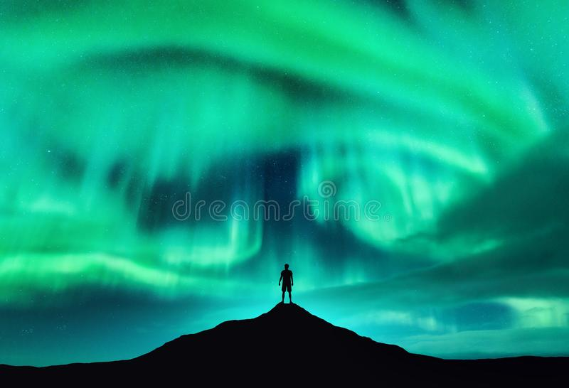 Aurora borealis et silhouette d'un homme sur la crête de montagne photographie stock libre de droits