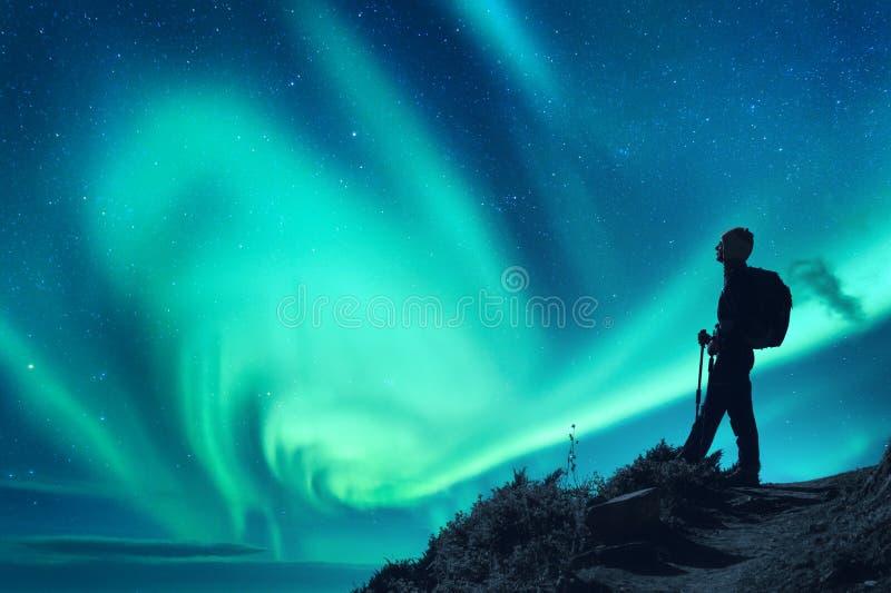 Aurora borealis et silhouette d'une femme avec le sac à dos la nuit image libre de droits