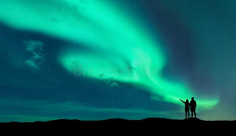 Aurora borealis et silhouette de l'homme et de femme photo stock