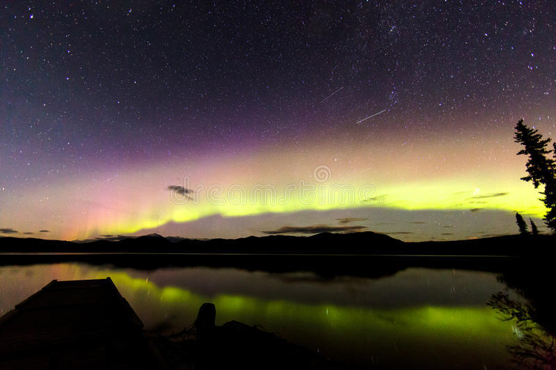 Aurora Borealis Green and Purple. Green and purple aurora borealis or northern lights, stars and satellites consumes the night sky. Beneath, a jetty penetrates stock photos