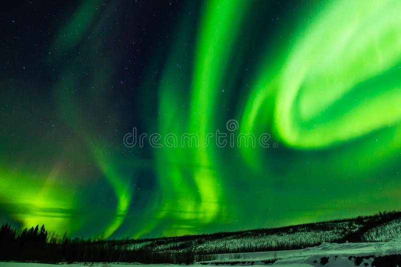Aurora Borealis. Greenish Dancing Swirls Of Northern Lights In Starry Sky royalty free stock image