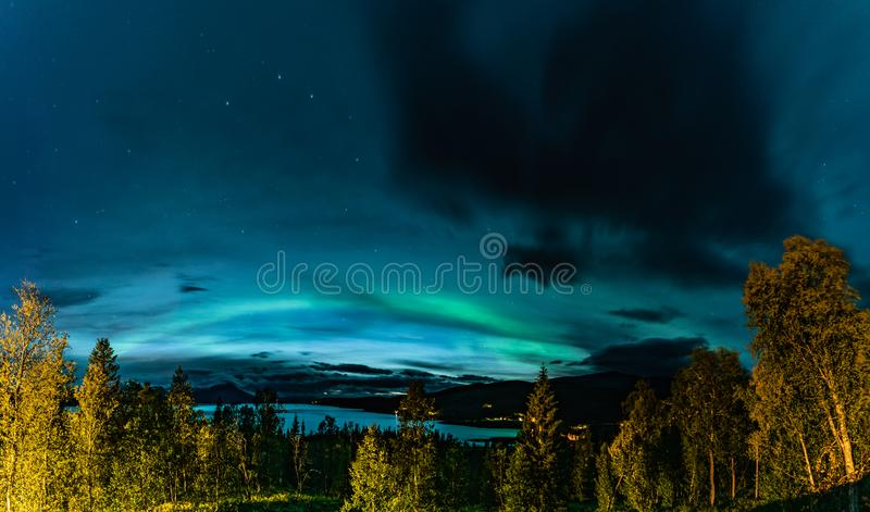 Aurora Borealis and heavy clouds over Norwegian mountains around Rossvatnet Lake, Northern Norway. Late summer night. Aurora Borealis and heavy clouds over stock image