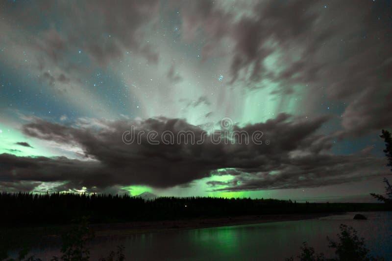 Aurora Borealis komt door wolken ver Alaska te voorschijn stock foto