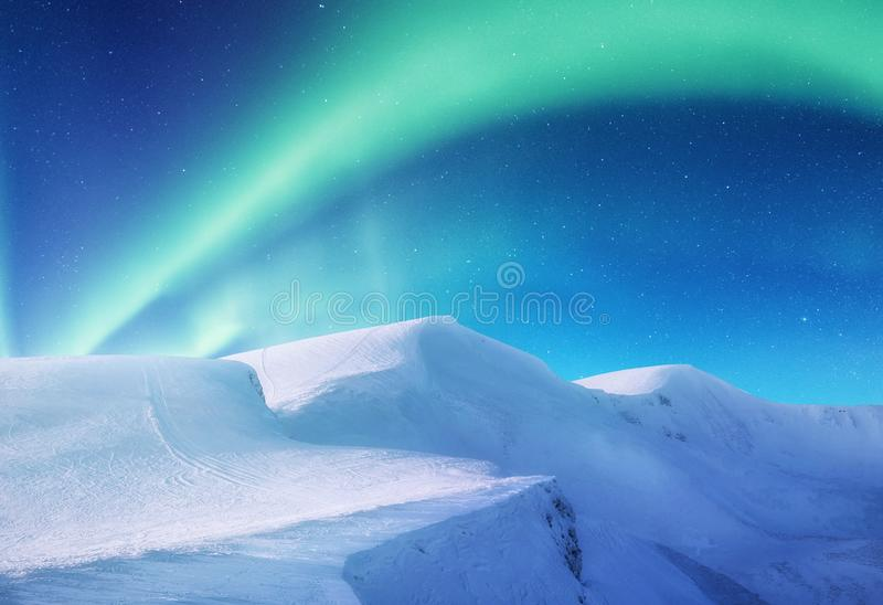 Aurora borealis on the Lofoten islands, Norway. Green northern lights above mountains. Night sky with polar lights. Night winter landscape with aurora. Natural royalty free stock photo
