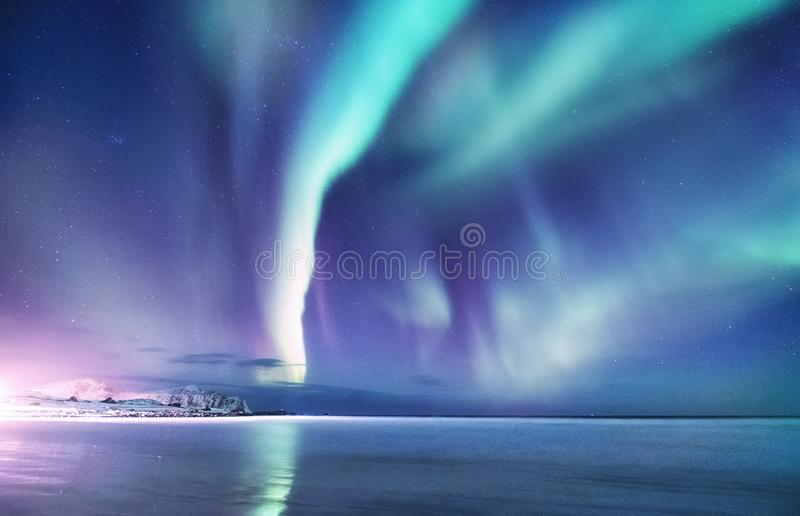 Aurora borealis on the Lofoten islands, Norway. Night sky with polar lights. Night winter landscape with aurora and reflection on. The water surface. Natural stock photography