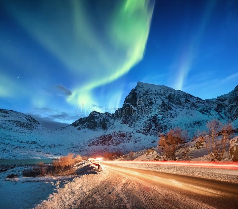 Aurora borealis on the Lofoten islands, Norway. Road traffic and blur car light. Green northern lights above mountains. Night sky. With polar lights. Natural stock images