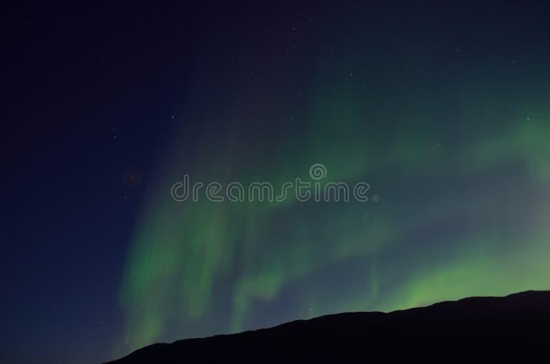 Aurora borealis massif dansant sur le ciel nocturne au-dessus de la montagne photo stock