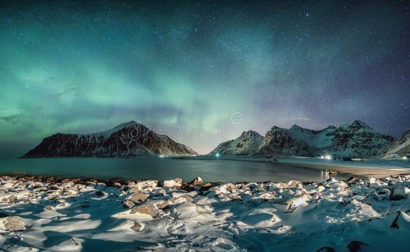 Aurora borealis mit Sternen über Gebirgszug mit schneebedeckter Küstenlinie an Skagsanden-Strand lizenzfreie stockfotografie