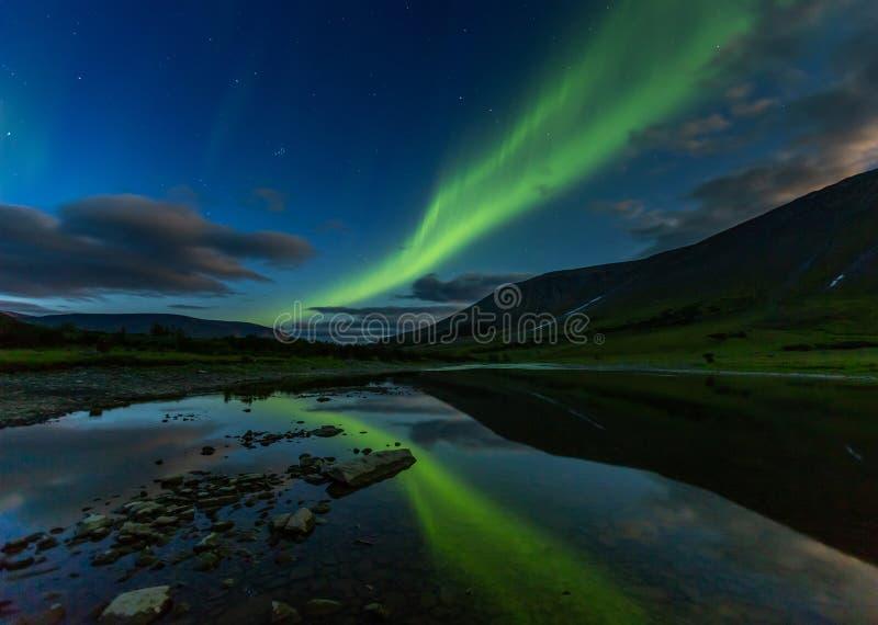 Aurora borealis in night sky cut mountains, reflected in water. Aurora borealis in the night sky cut the mountains, reflected in the water. Yamal. Russia royalty free stock photos