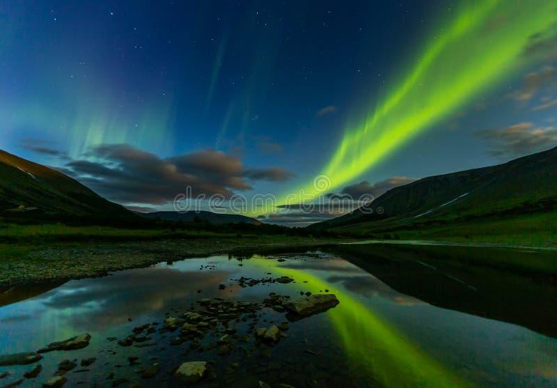 Aurora borealis in night sky cut mountains, reflected in water. Aurora borealis in the night sky cut the mountains, reflected in the water. Yamal royalty free stock photography