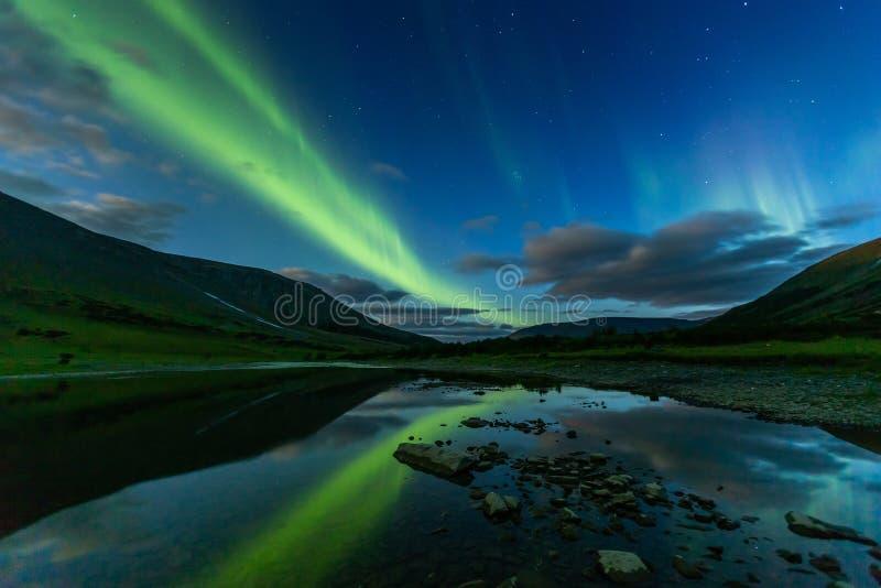 Aurora borealis in the night sky cut  mountains, reflected in. Aurora borealis in the night sky cut the mountains, reflected in the water. Yamal. Russia stock photos