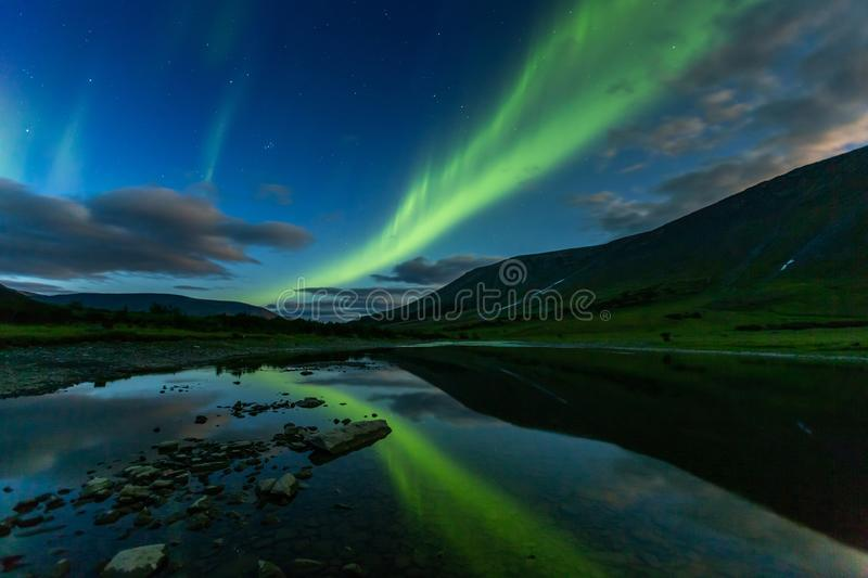 Aurora borealis in the night sky cut mountains, reflected in. Aurora borealis in the night sky cut the mountains, reflected in the water. Yamal. Russia royalty free stock photography