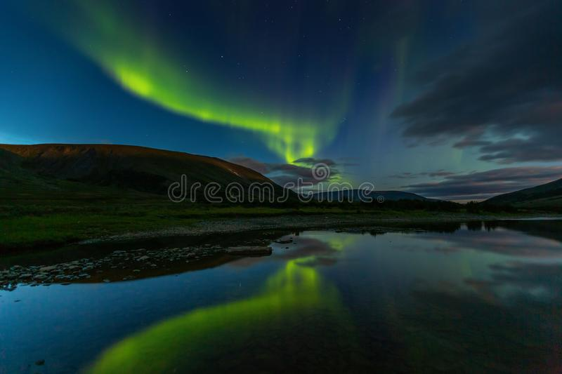 Aurora borealis in the night sky cut the mountains, reflected in. The water. Yamal. Russia stock photos