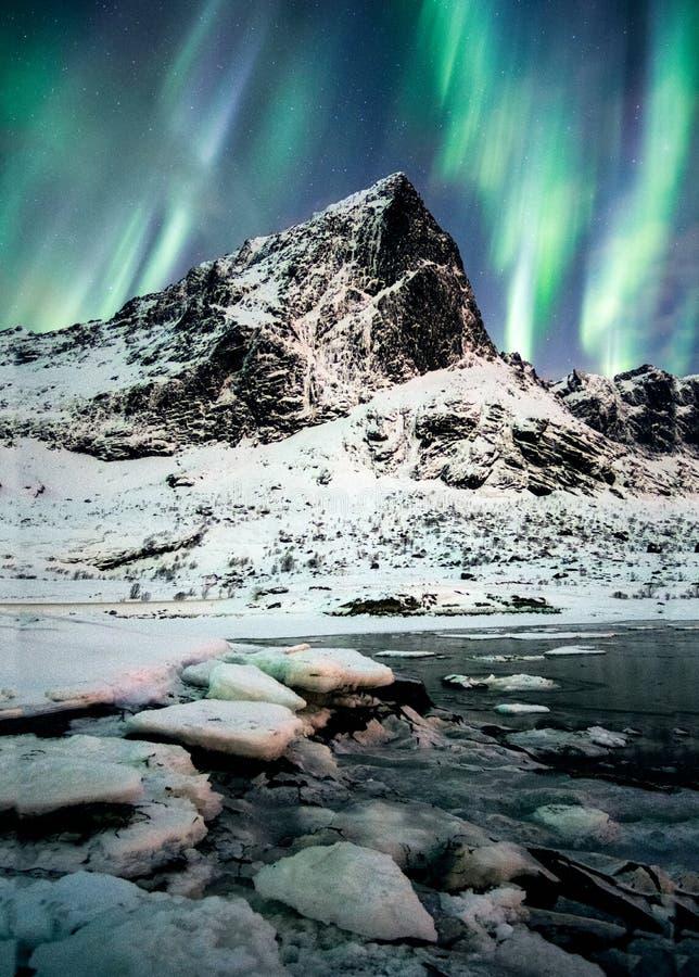 Aurora Borealis (nordliga ljus) explosion över berg i gl arkivfoton