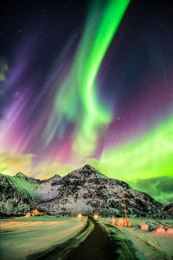 Aurora Borealis (Northern lights) explosion over mountains and r. Ural road at Skagsanden beach, Lofoten island, Norway royalty free stock photos