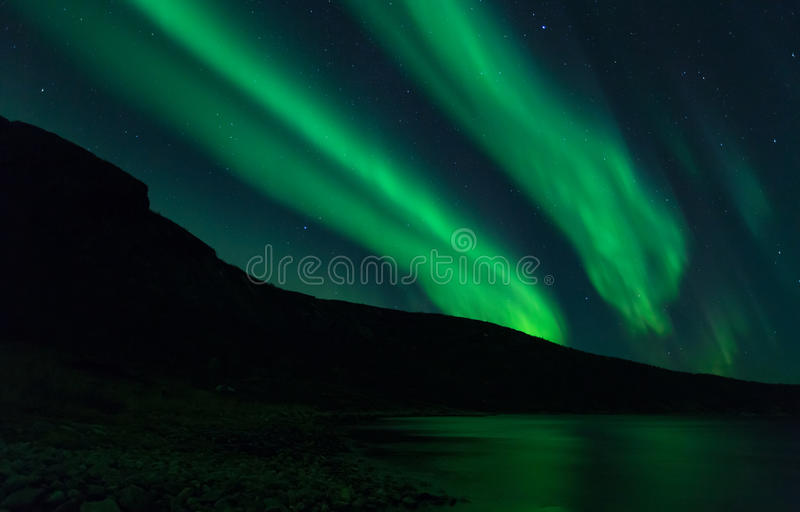 Aurora Borealis. In Northern Norway, green light lights up the scenery and makes the mountains pop out in silouette royalty free stock images
