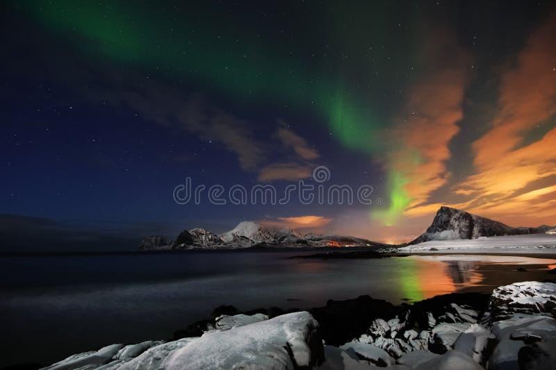 Aurora Borealis, o dragão verde que paira acima de uma praia snowcovered na ilha de Flakstad, Lofoten imagens de stock