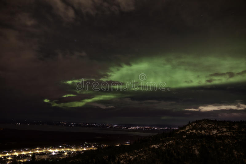 Aurora Borealis over Eagle River. Aurora Borealis as a glowing green light at night in the cloudy sky over Eagle River, Alaska, United States of America royalty free stock images
