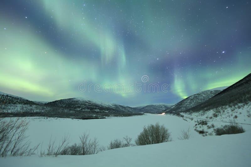 Aurora borealis over snowy winter landscape, Finnish Lapland stock photo