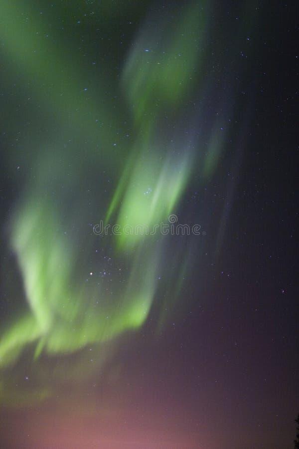 Aurora borealis over town lights glow royalty free stock image