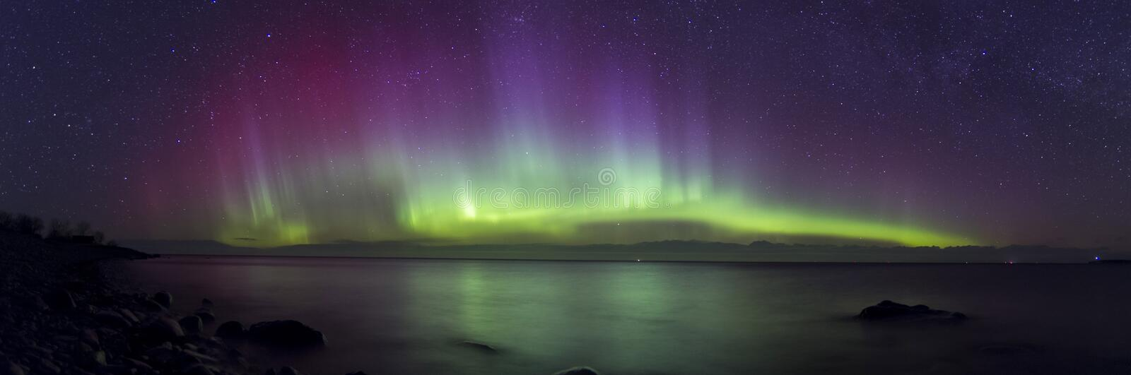 Aurora Borealis panorama and beautiful reflections. It is rare to see aurora without ice and snow. Panorama is daken during powerful geomagnetic storm in Saremaa stock image