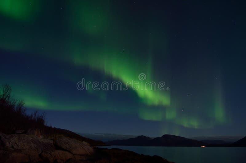 Aurora borealis poderoso que dança no céu noturno sobre a montanha e a paisagem do fiorde no outono atrasado fotografia de stock royalty free
