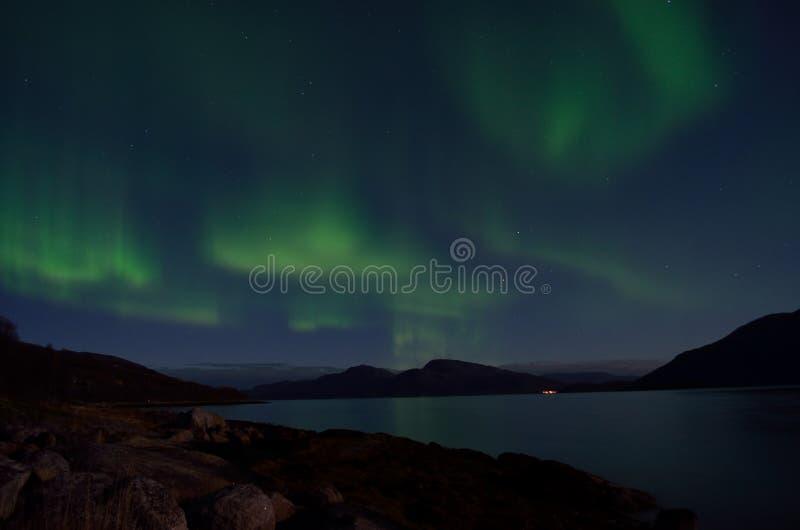 Aurora borealis poderoso que dança no céu noturno sobre a montanha e a paisagem do fiorde no outono atrasado imagens de stock royalty free