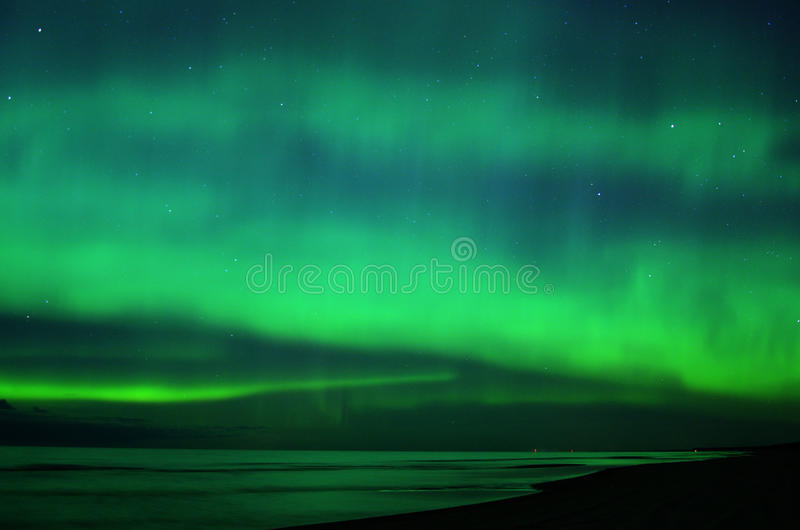 Night sky stars magic aurora polar lights over sea royalty free stock images