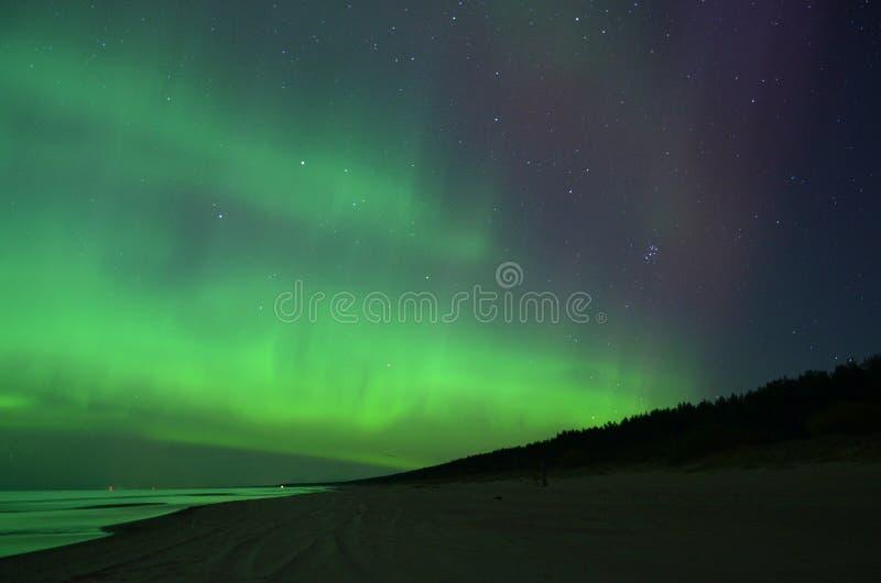Stars and aurora northern polar lights night sky. Aurora borealis polar lights and night sky stars over sea royalty free stock photos