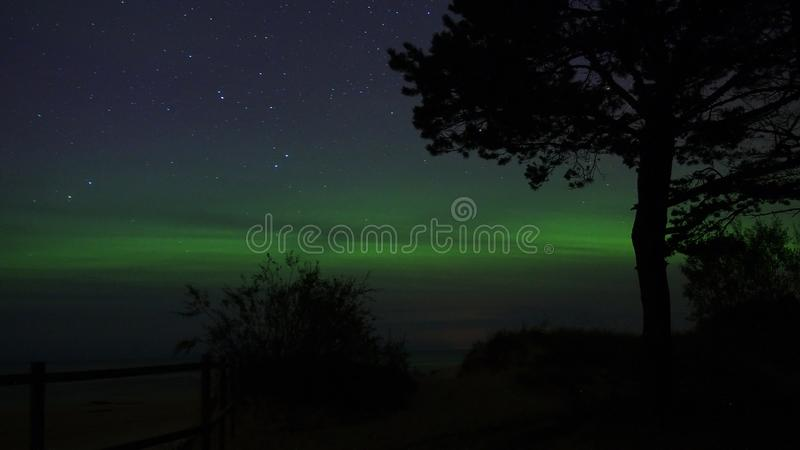 Night sky stars and aurora polar lights. Over sea stock photography