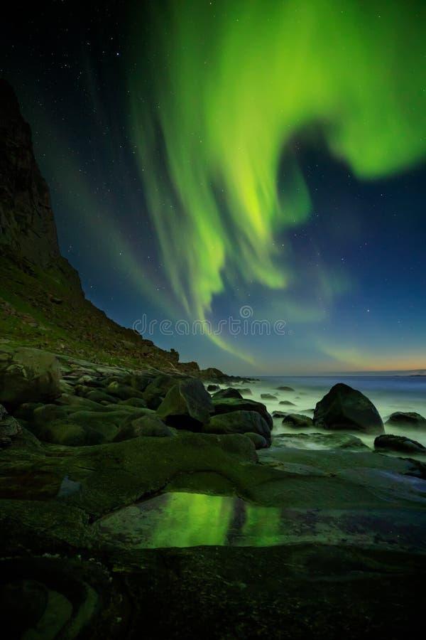 Aurora Borealis reflejó en una piscina de la roca, playa de Utakleiv imágenes de archivo libres de regalías