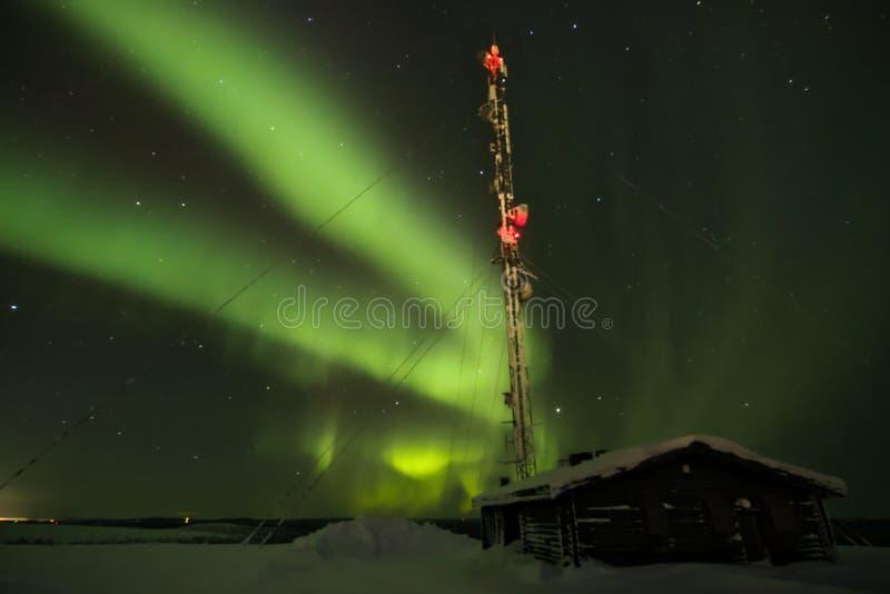 Aurora borealis sobre una cabaña en la distancia en el horizonte foto de archivo