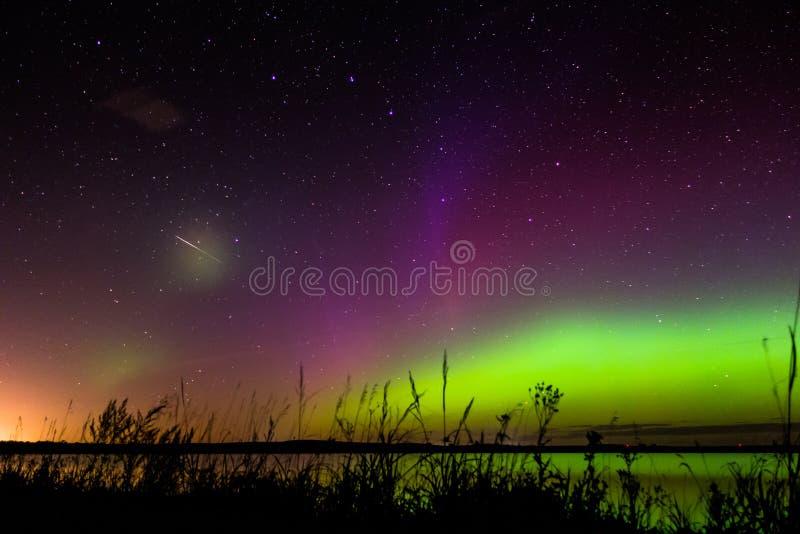 Aurora borealis verde, magenta y púrpura con el meteorito imágenes de archivo libres de regalías