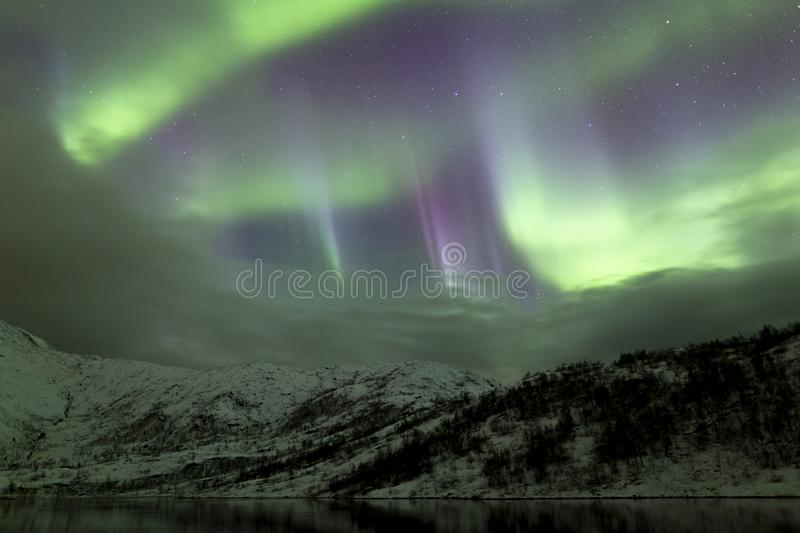 Northern lights of scandinavia. Aurora borealis and winter landscape, snowcovered mountains and hills nearby lake. cold northern norway stock images