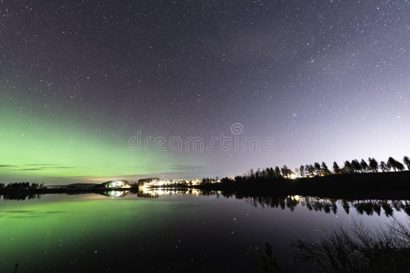 Aurora en sterren reflecteren aan de linkerkant van het meer, bebossing, nachtelijk Scandinavisch platteland, herfst stock afbeeldingen