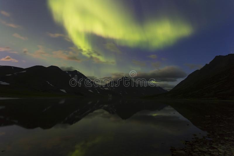 Aurora in the night sky cut the mountains, reflected in the water. Yamal. Russia stock photo