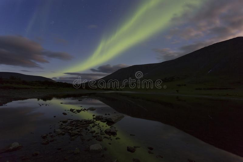 Aurora in the night sky cut the mountains, reflected in the water. Yamal. Russia stock photos