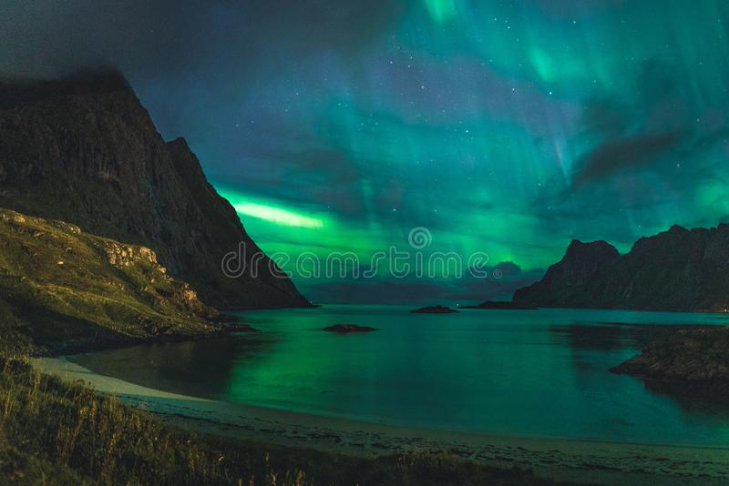 Aurora over sandy beach haukland, Kvalvika and Skagsanden with stones in Norway, Lofoten islands. Northern lights in royalty free stock image