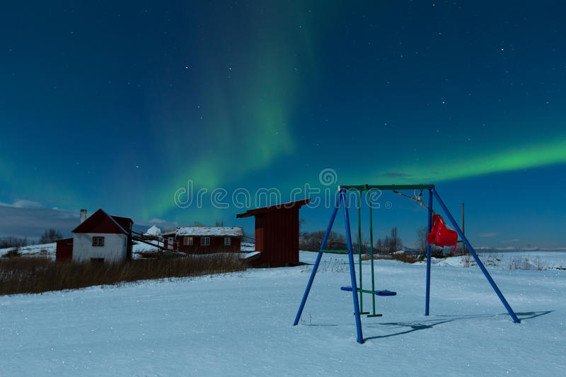 Playground. Weak aurora and moonlit landscape covered in snow with playground in focus royalty free stock image