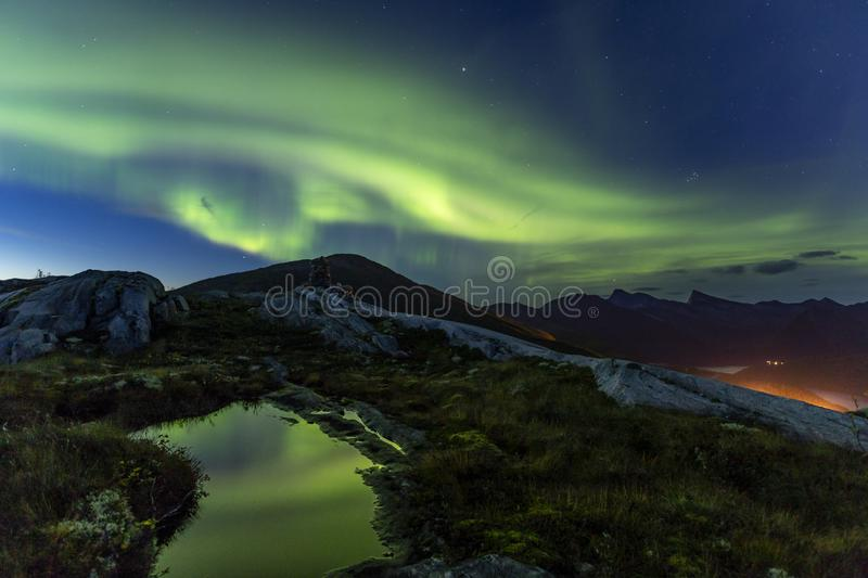 Aurora and pond on mountain. Green Aurora Borealis across beautiful autumn night landscape in norway with reflections in a small pond blue deep sky stars and royalty free stock image